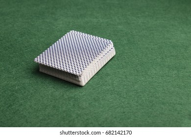 A deck of playing-cards face down on a green baize background