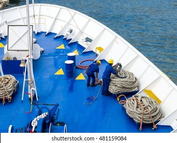 Deck sailors wearing blue overall and yellow hardhat working with ropes on blue deck of a ship during mooring operation. No release required.
