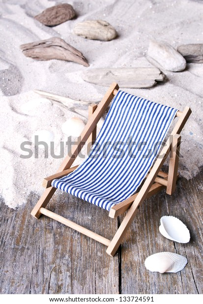 Deckchair, shells and sand/beach/holiday