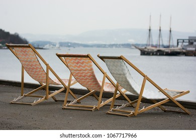 Deckchairs left on the quay in gray and cold weather. Facing a sailing ship. symbolizing a longing for summer and travel. Dreaming of travel and vacation.