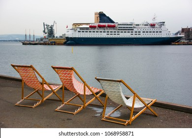 Deckchairs left on the quay in gray and cold weather. Facing a cruise ship, symbolizing a longing for summer and travel. Dreaming of travel and vacation.