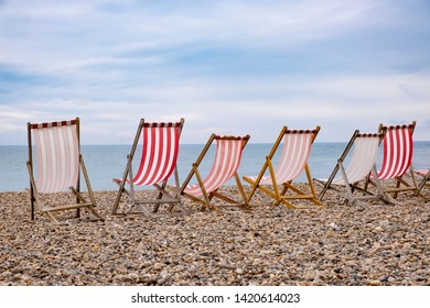Deckchairs on beach, typical english seaside holiday scene, red and white stripes