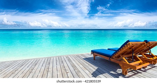 deckchairs on jetty in front of tropical island