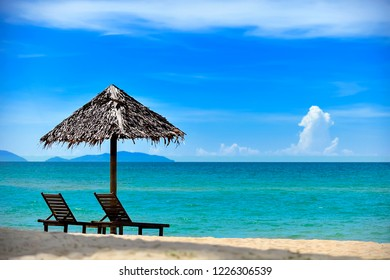 Deckchairs under the thatched roof on a beach, a tourist destination in Kampung Mangkok, Setiu, Terengganu, Malaysia. Clean sandy beach with blue sea and clear blue sky.