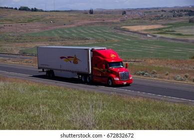 """Decker"" A Red Peterbilt Semi-Truck pulling a white branded trailer along a rural Oregon Highway.  June 20th, 2017 Rural Oregon, USA"
