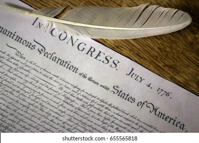Declaration of Independence with feather quill on wood surface