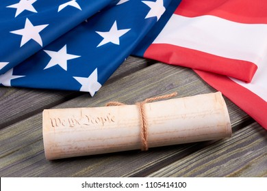 Declaration of the Independence of the United States. Close up vintage constitution of the USA and USA flag on wooden background. Documents of the country.