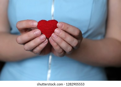 Declaration of love, woman with Valentine heart close up. Female hands holding red knitted heart, concept of romance, health care or blood donation