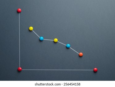Decline graph concept made of colorful button shaped candies over dark blue background. This image is a photograph with a drawing over it.