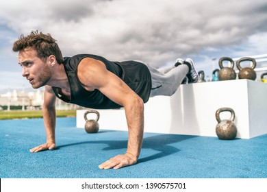 Decline push Up fitness man doing strength training exercise pushup at outdoor gym with elevated legs on jump box.