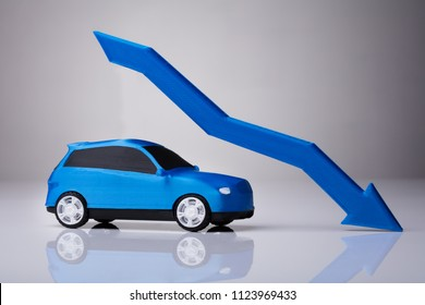 Declining Arrow Over Blue Car Against Gray Background