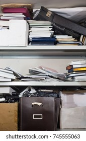 Declutter concept - lots of books, papers, boxes on shelf - chaos, clutter, mess, unorganized - vertical