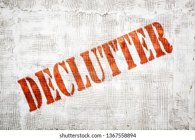 declutter - red graffiti style sign on a white stucco wall