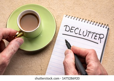 declutter word - man hand writing a note with a black marker in a spiral notebook with a cup of coffee