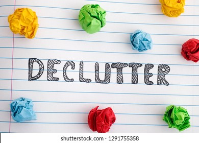 Declutter. The word Declutter on notebook sheet with colorful crumpled paper balls around it. Close up.