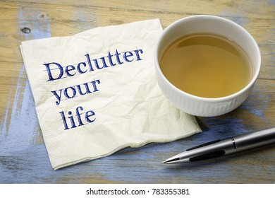 declutter your life - motivational handwriting on a napkin with a cup of tea