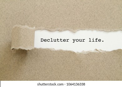 Declutter your life word written under torn paper.
