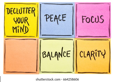 Declutter your mind for clarity, peace, focus and balance - handwriting on an isolated set of sticky notes
