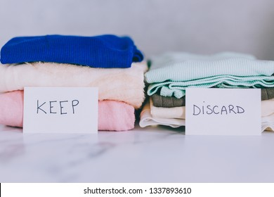 decluttering and tidying up concept: piles of tshirts and clothes being sorted into Keep Discard and Donate categories