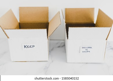 decluttering and tidying up conceptual still-life, white storage boxes to sort between objects to keep and those to declutter or donate with respective labels