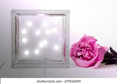 Deco glass block with pink peony and lighs inside, mockup on a table. Interior photography.