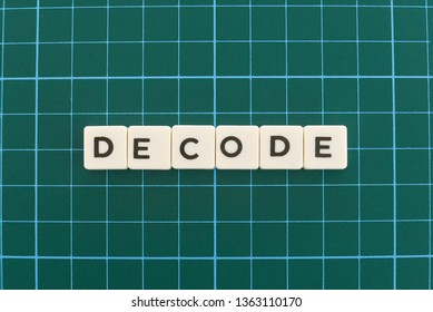 Decode word made of square letter word on green square mat background.