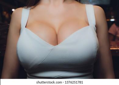 Decollete, female breast. Neckline white dress and fur collar.