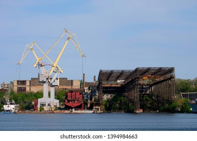 A decommissioned navy construction port with industrial cranes and abandoned, rusty structures in Mykolayiv, Southern Ukraine.