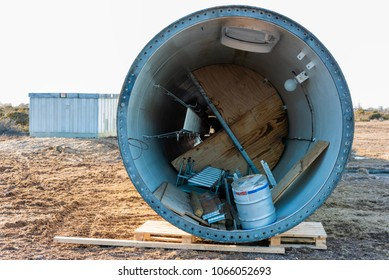 Decommissioned wind turbine tower lying on the ground awaiting transport.