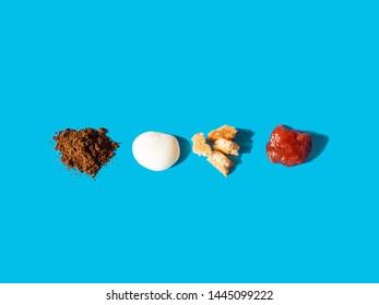 Deconstructed breakfast on blue background. Food elements - ground coffee, yogurt, toasted bread, strawberry jam. Harsh light
