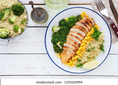 Deconstructed healthy chicken and couscous salad with broccoli florets and corn