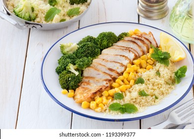 Deconstructed healthy chicken and couscous salad with broccoli florets and corn or Budda bowl