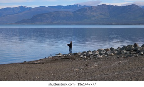 Deconstruction Bay, Yukon Territories / Canada - 06/07/2017: Man Fishing for trophy fish at the Southern End of Lake Kluane; Saint Elias Mountains are visible and the lake is in Kluane National