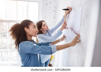Decor connoisseurs. Cheerful female friends handing a picture on the wall together, one of the girls holding the picture and the other one hammering in a nail