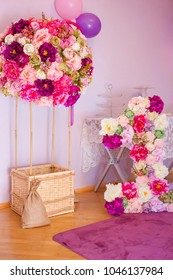 Decor for the first child's birthday, air balloon with basket decorated with flowers and a number one, decorated with brightly colored flowers. Cake smash.