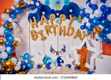 Decor of golden balloons for a little boy's birthday celebration. Happy Birthday written by bouncy balloons. The very first holiday in the life of the baby. Decorated photo zone with balls and stars