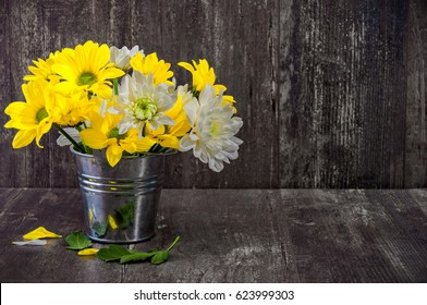 Decor houses, yellow and white chrysanthemums, beautiful flowers in vases on a wooden vintage table on a gray background, antique photography, retro interior with flowers.