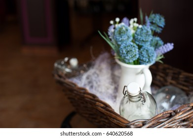 Decor in the interior. Empty wine bottle in a wicker basket with flowers