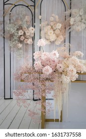 Decor for a luxury holiday wedding. Floral decoration with blooming flowers of peonies, roses, gypsophila and calla lily in white and pink colors.