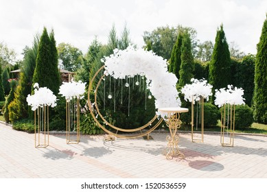 The decor of the marriage registration of marriage wedding outdoors, Golden columns, round and white flowers