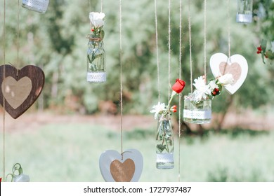 Decor for outdoor wedding photo shoots. Decorated photo zone in nature. Mini-vases and bouquets of flowers.