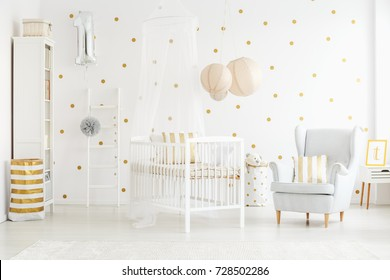 Decor pillow on grey armchair in bright newborn baby's interior with lanterns above bed