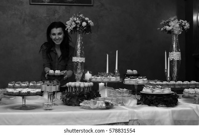 decorate a festive table with sweets and a variety of sweet snacks against the backdrop of  a girl confectioner