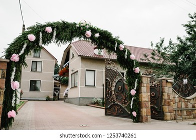 The decorated arch of flowers and the entrance gate, the courtyard with the house. Morning preparations for a wedding day.