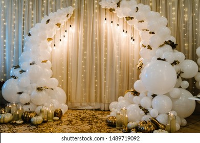 Decorated arch for wedding ceremony. White balloons, candles, autumn leaves and small pumpkins. Autumn location and Halloween decor. Selective focus.