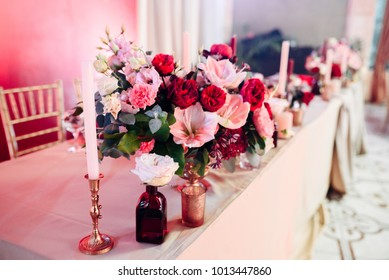 Decorated area in gold and burgundy colors with white candles and flowers