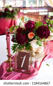 Decorated area in gold and burgundy colors with white candles and flowers, with table number