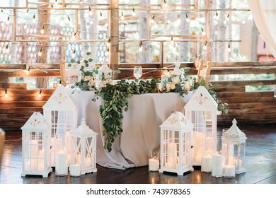 Decorated area with white wooden candle lamps and flowers