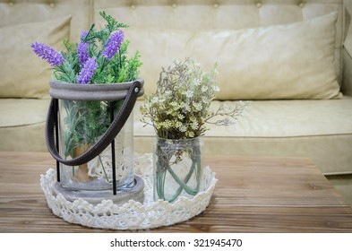 Decorated artificial flowers on wooden table with sofa background in living room