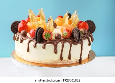 Decorated Biscuit Cake With Cream Cheese, Berries, Fruits, Chocolate On Turntable, Blue Background. Side View.